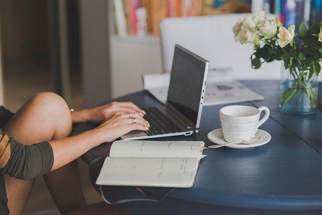 Kobieta siedzi przed komputerem z kawą