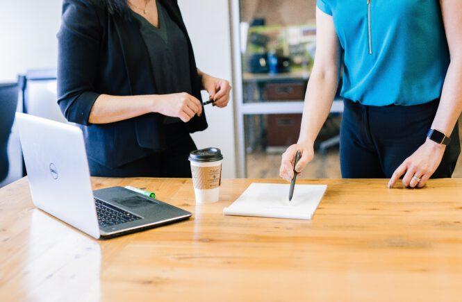 rozmowa dwóch ludzi dokumenty i laptop na biurku